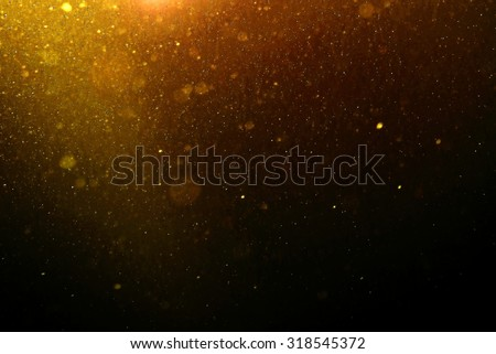 Abstract gold background with floating and reflecting dust blur - stock photo