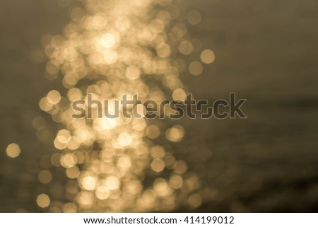 Abstract golden sunlight bokeh on blue sea water background. - stock photo