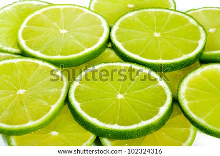Abstract green background with citrus-fruit of lime slices. Close-up. Studio photography. - stock photo