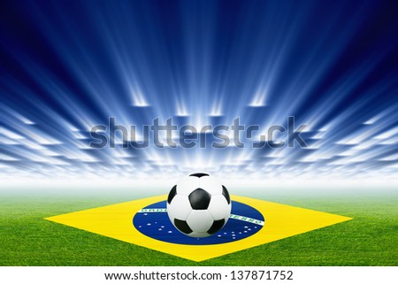Abstract green soccer stadium, soccer ball, bright spotlights, Brazil flag - stock photo