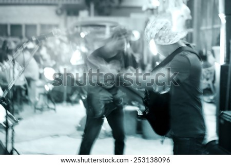abstract guitarist on street walk at night, blue tone and motion blur concept - stock photo