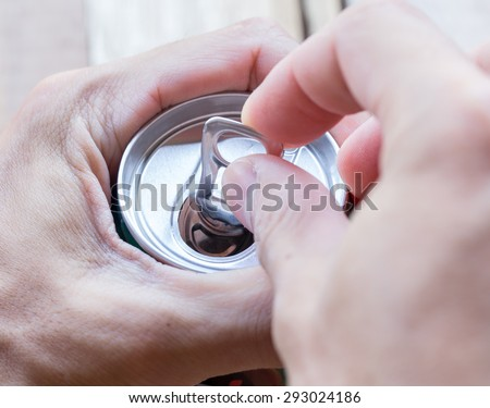 Abstract hand man open cans. - stock photo