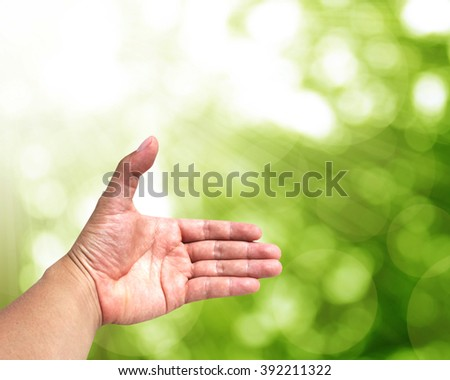 abstract Hand with Green leaf background bokeh. Natural beauty created by human hands.The means of cooperation in the creation of nature. Pure and simple living in natural surroundings.