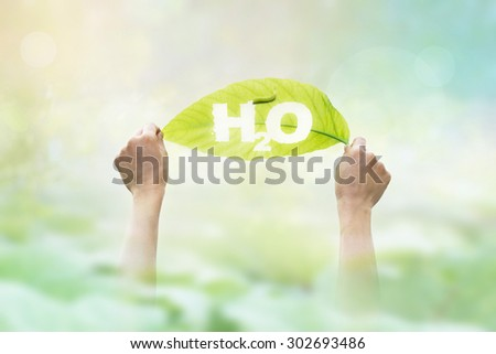 abstract, holding a green leaf in the word H2O on vibrant nature background