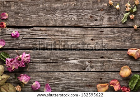 Abstract holiday frame with rose petals and dried flowers on old wooden plates. - stock photo