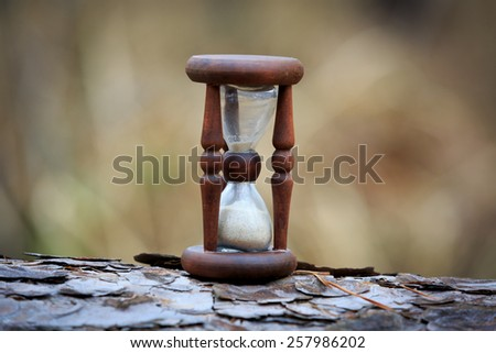 abstract hourglass on wooden log surface - stock photo