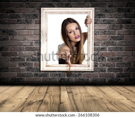 Abstract image of a beautiful woman trapped in a picture frame over a brick wall background. - stock photo