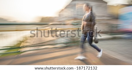 Abstract image of a woman walking down the street. Intentional motion blur - stock photo