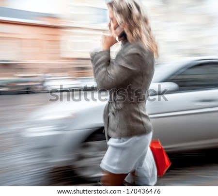 Abstract image of a young woman talking on a mobile phone on a city background with car. Intentional motion blur - stock photo