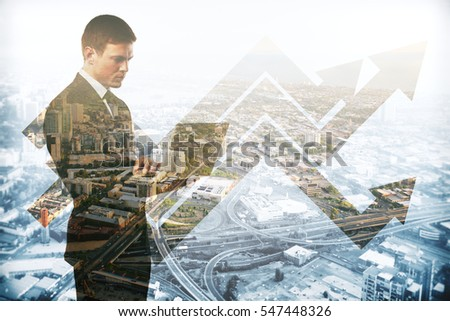 Abstract image of caucasian businessman using laptop on city background with business charts. Double exposure. Success concept