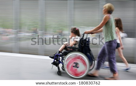 abstract image of child with disabilities in a wheelchair, accompanied and modern style with a blurred background - stock photo