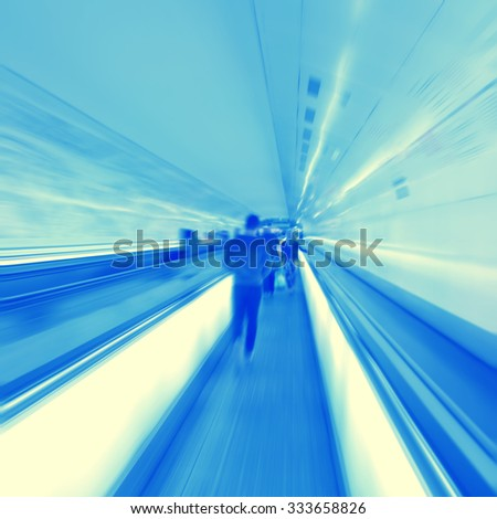 Abstract image of moving walkway and blurred people. - stock photo