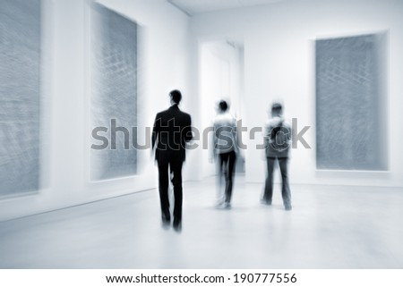 abstract image of people in the lobby of a modern art center with a blurred background and blue tonality