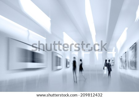abstract image of people in the lobby of a modern art center with a blurred background and blue tonality - stock photo