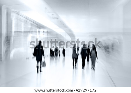 abstract image of people in the lobby of a modern business center with a blurred background and monochrome blue tonality