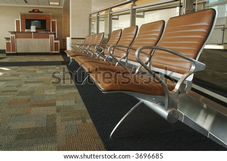 Abstract image of stylish designed waiting room seating and gate desk at an airport.