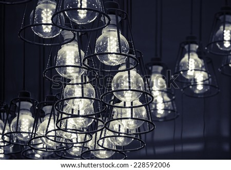 Abstract interior fragment. Stylized vintage illumination with modern LED lamps in metal lampshades, black and white photo - stock photo
