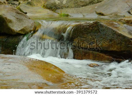 Abstract landscape of the fast flowing water in the mountain river. Light reflection on the turbulent water flow. Water captured with motion blur and illuminated by reflected color from sunlit trees. - stock photo