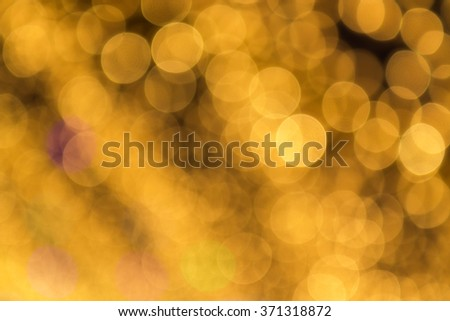 Abstract light celebration blur background with defocused, golden lights.