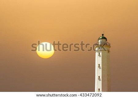 Abstract lighthouse at the seashore at the sunset - stock photo
