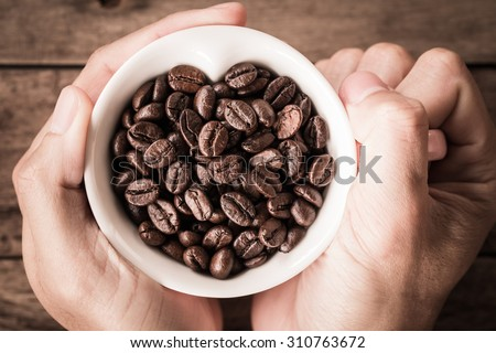 Abstract Love Coffee cup and beans on hand wooden background. - stock photo