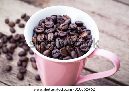 Abstract Love Coffee cup and beans on  wooden background.  - stock photo