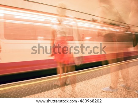 Abstract low point of view transport background blurred images of waiting on platform commuters and train moving in station typically modern urban life.
