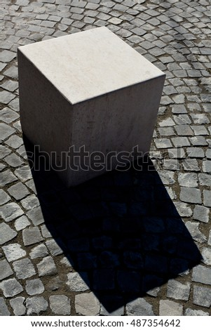 Abstract marble cube on cobblestone, urban architecture