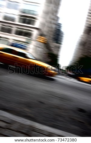 Abstract motion blur of a city street scene at night with a yellow taxi cab speeding by. - stock photo