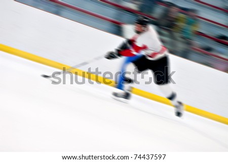 Abstract motion blur of a hockey player handling the puck as he speeds down the ice. - stock photo