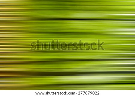 Abstract motion blur of trees in a green forest in spring time - stock photo