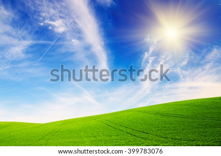 Abstract natural idyllic background with green grass, sun shining  and cloudy blue sky
