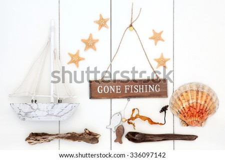Abstract nautical background with gone fishing sign, driftwood, starfish and scallop shells, seaweed and decorative wooden boat over white wood. - stock photo