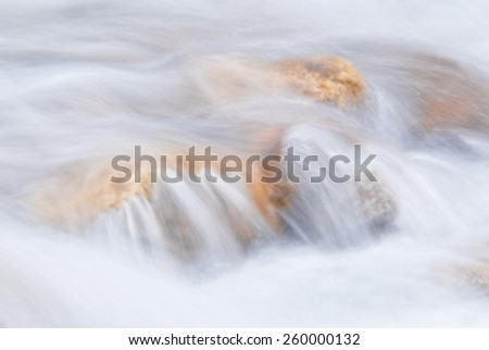 Abstract of a swiftly moving stream. - stock photo
