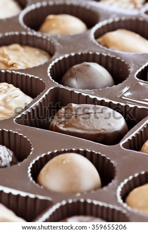 Abstract of a variety of milk and dark chocolate candies. Extreme shallow depth of field with selective focus on center candy. - stock photo