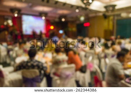 Abstract of blurred people sitting in banquet hall - stock photo