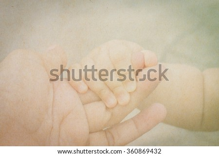 Abstract of paper texture of new born baby hand with mother hand in vintage tone style