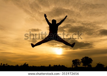 abstract of silhouette man is jumping high in front of orange sky background.