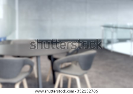 abstract office with meeting round table and black office chairs for conference, blur background - stock photo