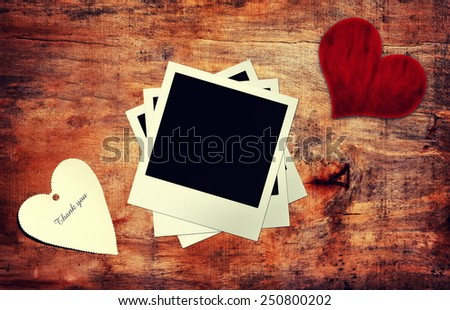 abstract paper heart and instant photo  on wooden table - stock photo