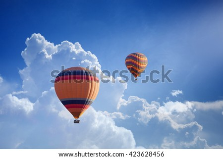 Abstract peaceful background - hot air balloons flies in blue sky with white clouds - stock photo