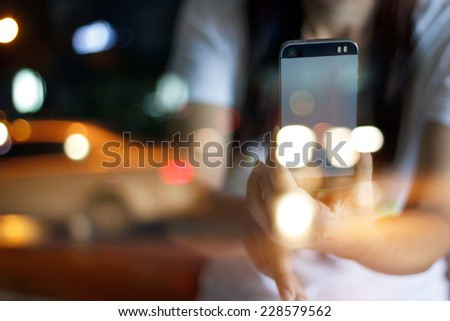 Abstract people take picture through glass by smart phone on street, soft and blur concept for background - stock photo