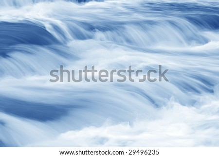 Abstract perspective of a swiftly moving stream in shades of blue.