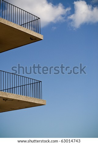 abstract photo of two minimalistic identical balconies against a blue sky. - stock photo