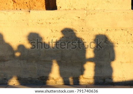 Abstract picture and pattern of shadows of people who are walking on the street in Montpellier France. Their human forms can be seen on the textured surface of an old stone wall lighted by the sun.