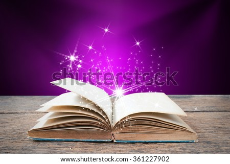 Abstract purple magic book on wooden background - stock photo