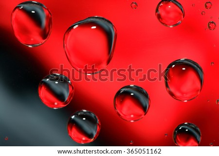 Abstract red and black background with various water drops - stock photo