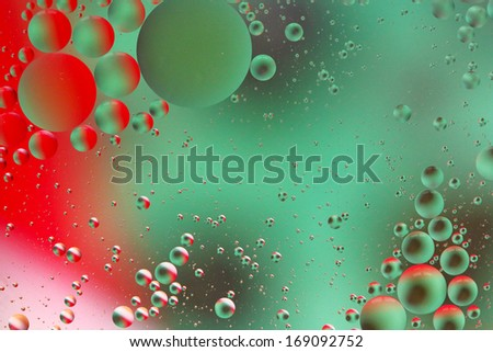 Abstract red and green bubbles - oil on water - stock photo