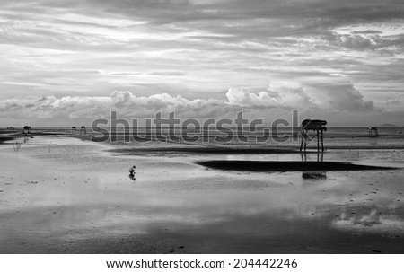 Abstract scene lonely man on Vietnam beach under cloudy sky, watch tower on black sand at Mekong Delta beach  - stock photo