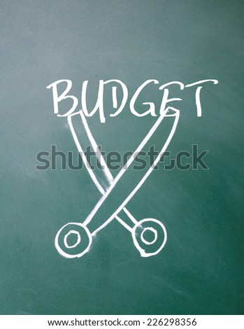 abstract scissors cut budget symbol on blackboard - stock photo